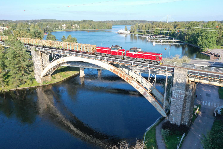 Kaksi punavalkoista dieselveturia vetää perässään pitkää puutavarajunaa sillan päällä vesistön yläpuolella.