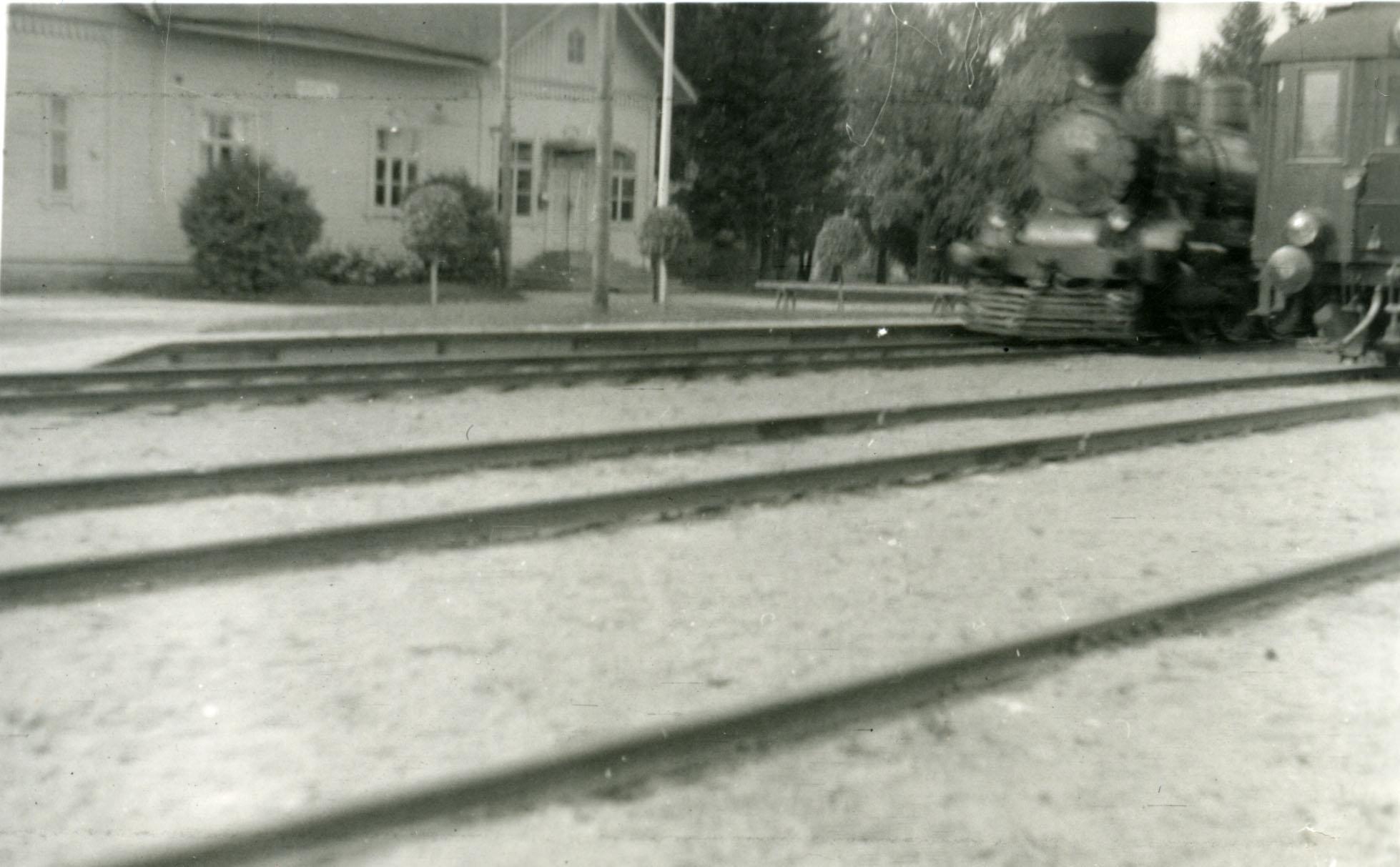 Epäterävä kuva asemasta. Kuvan oikeassa laidassa näkyy hieman höyryveturia ja moottorivaunun päätyä.