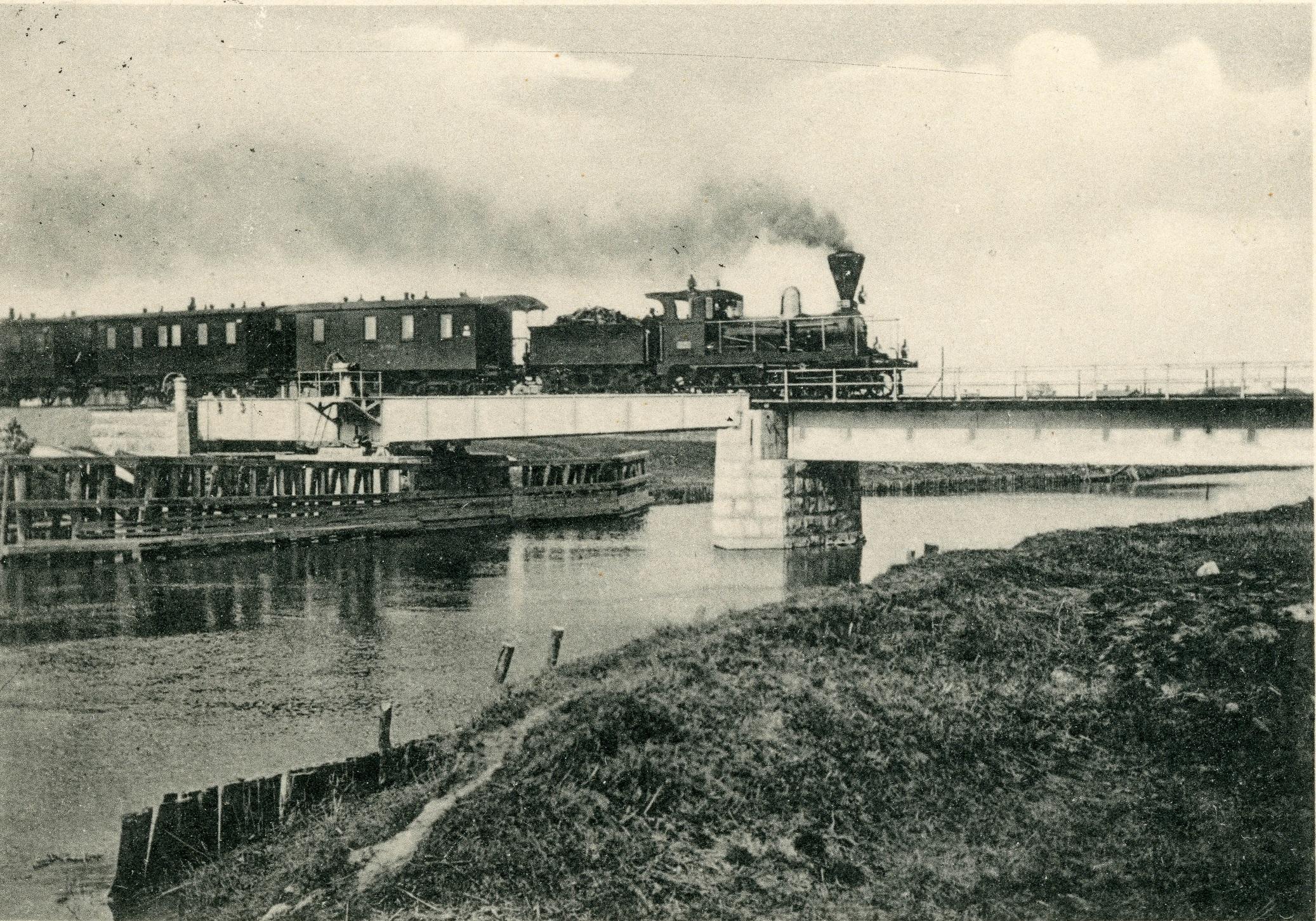 Sillalla vanhanaikainen höyryveturi ja matkustajavaunuja.