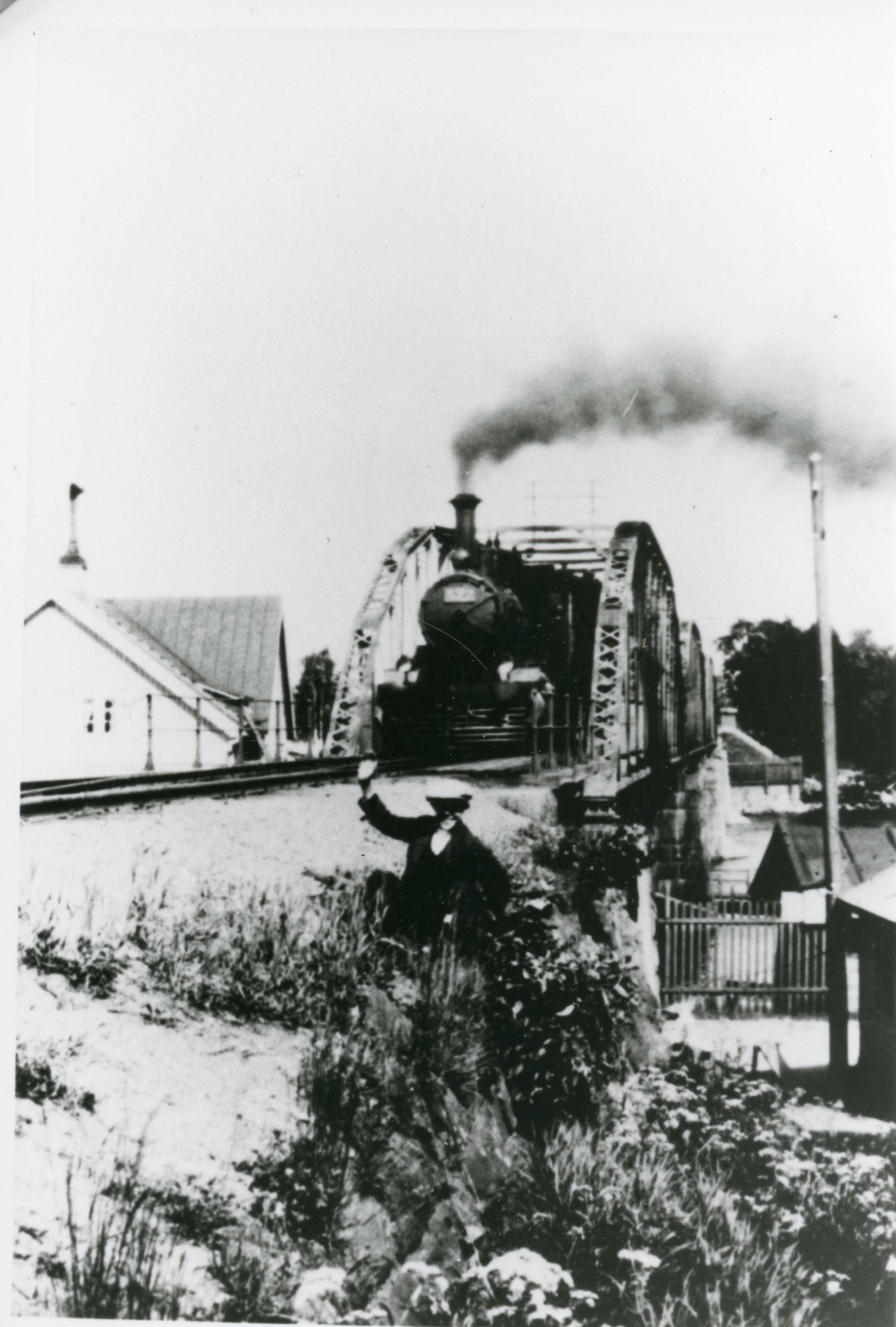 Höyryveturi tulossa sillalta, etualalla penkereellä kasvillisuuden seassa mies käsi pystyssä. Radan molemmin puolin rakennukset.