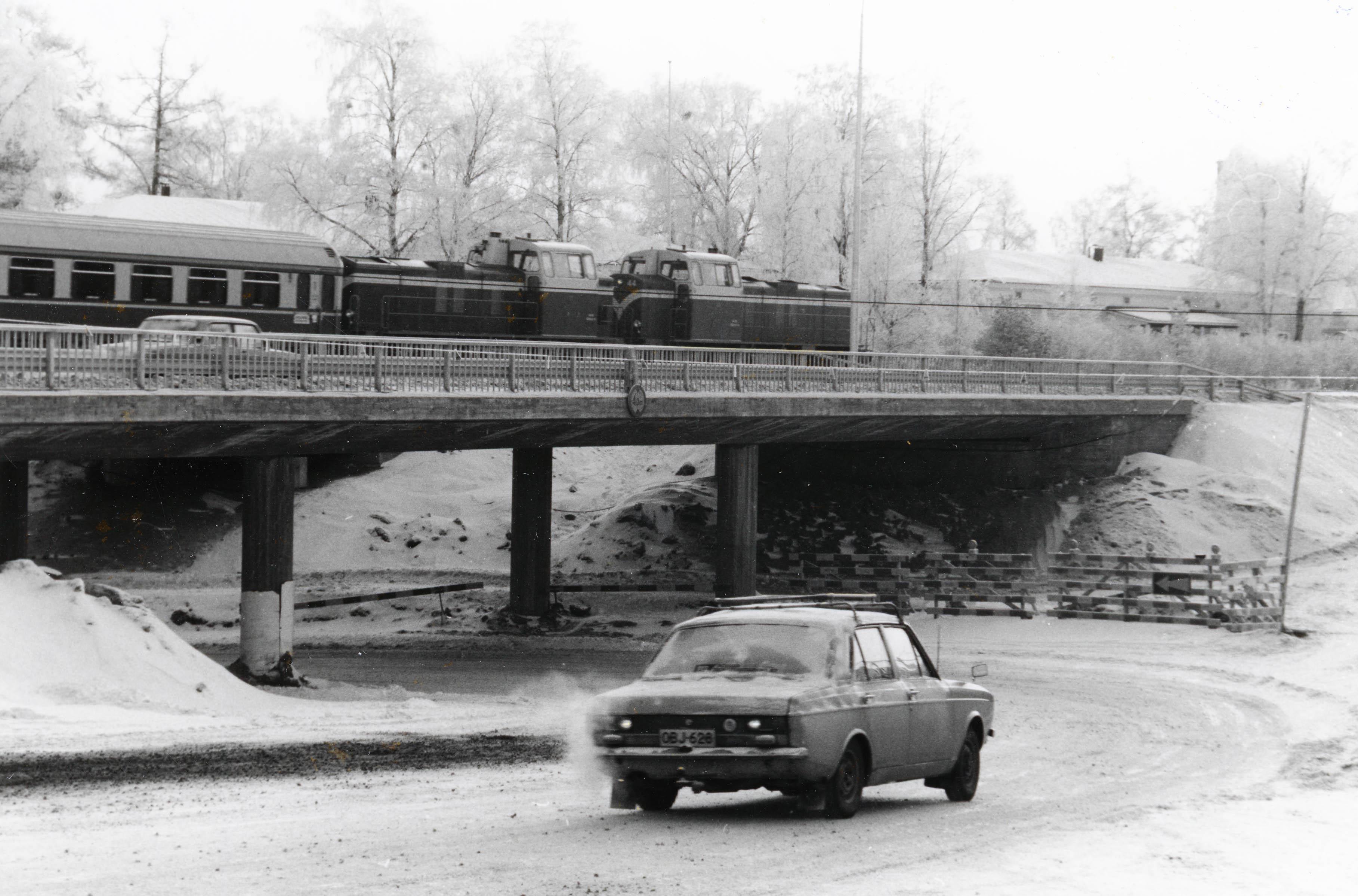 Kaksi dieselveturia ja matkustajavaunu sillalla, sillan alle on ajamassa auto mutkassa.