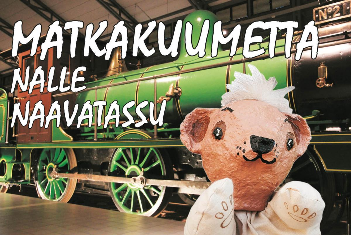 Käsiteatterinukke Nalle Naavatassu vihreän tavaraliikenneveturin edessä Suomen Rautatiemuseon näyttelyhallissa.