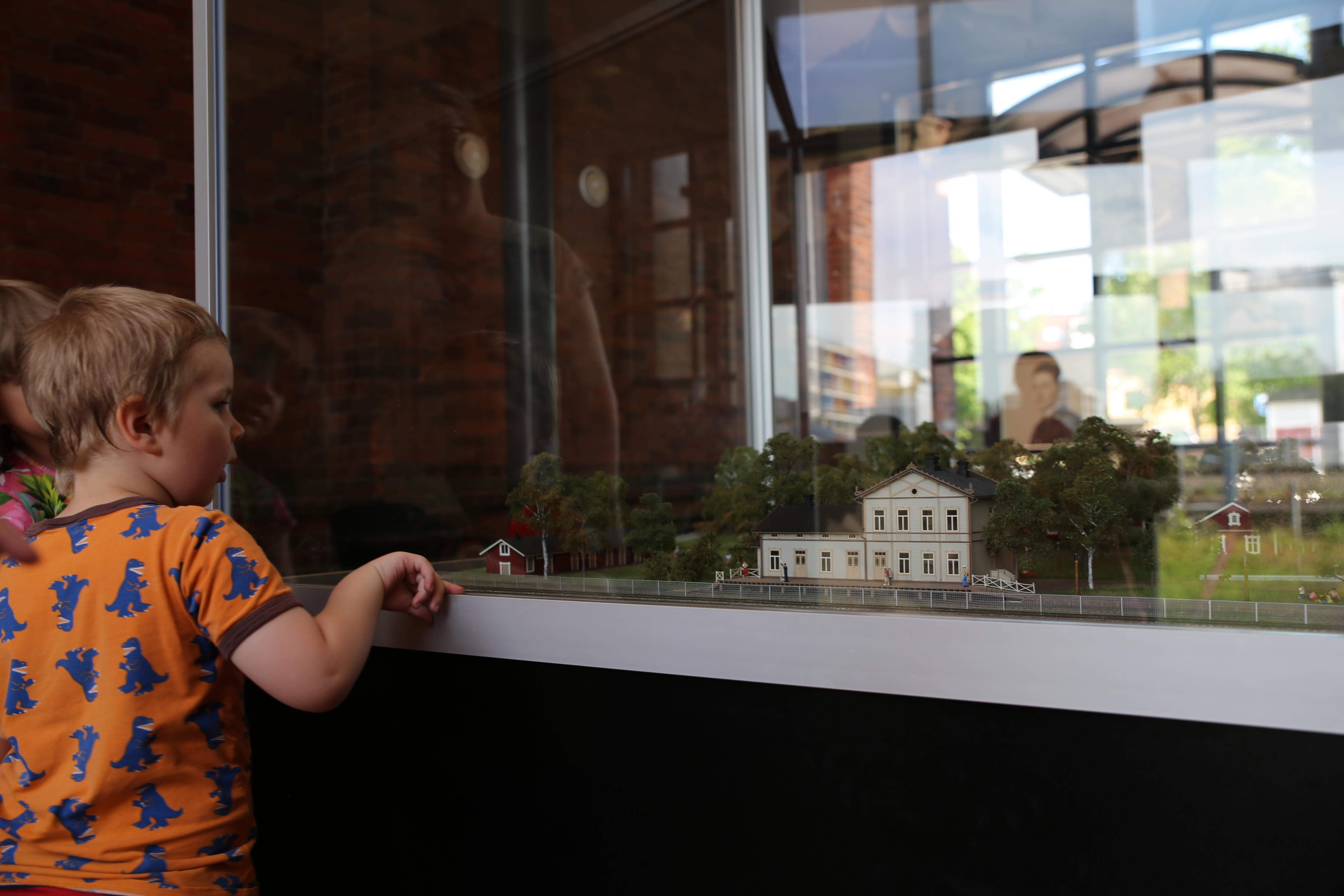 Poika tutkii Rautatiemuseon alueen pienoismallia Rautatiemuseon aulassa.