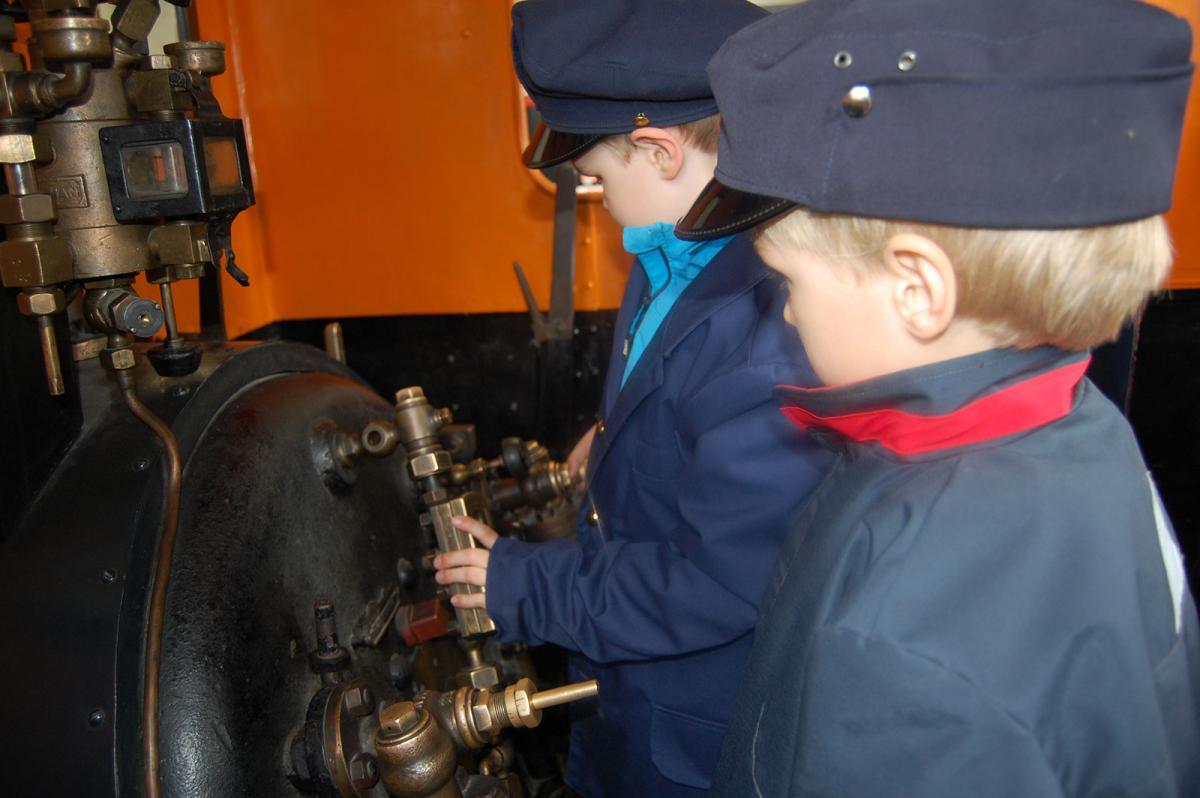 Kaksi nuorta poikaa tutkivat veturin mekaniikkaa