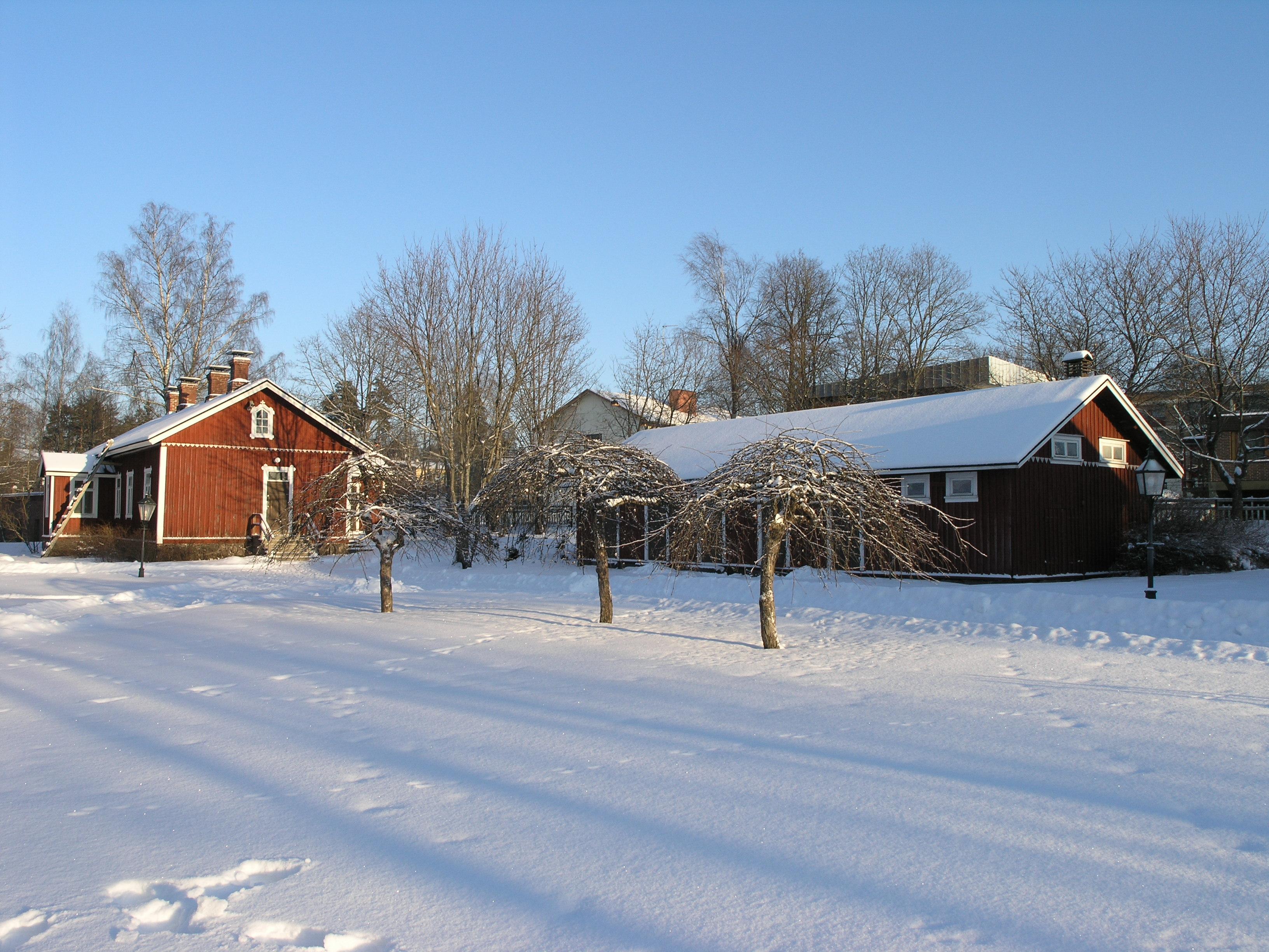 Kasarmi ja liiteri Rautatiemuseon puistossa talvisen maiseman keskellä.