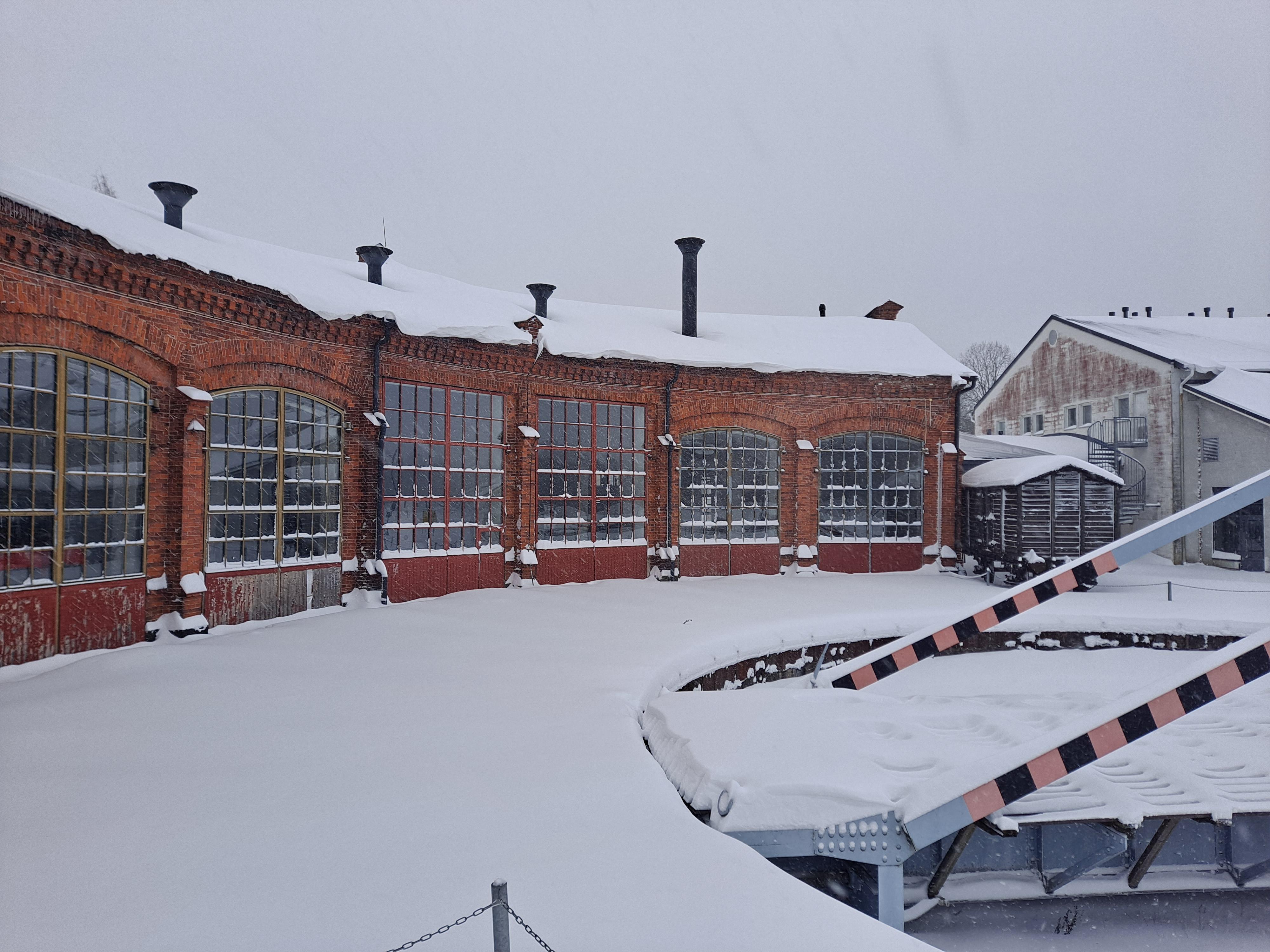 Rautatiemuseon veturitalli ja kääntöpöytä lumisena talvipäivänä.