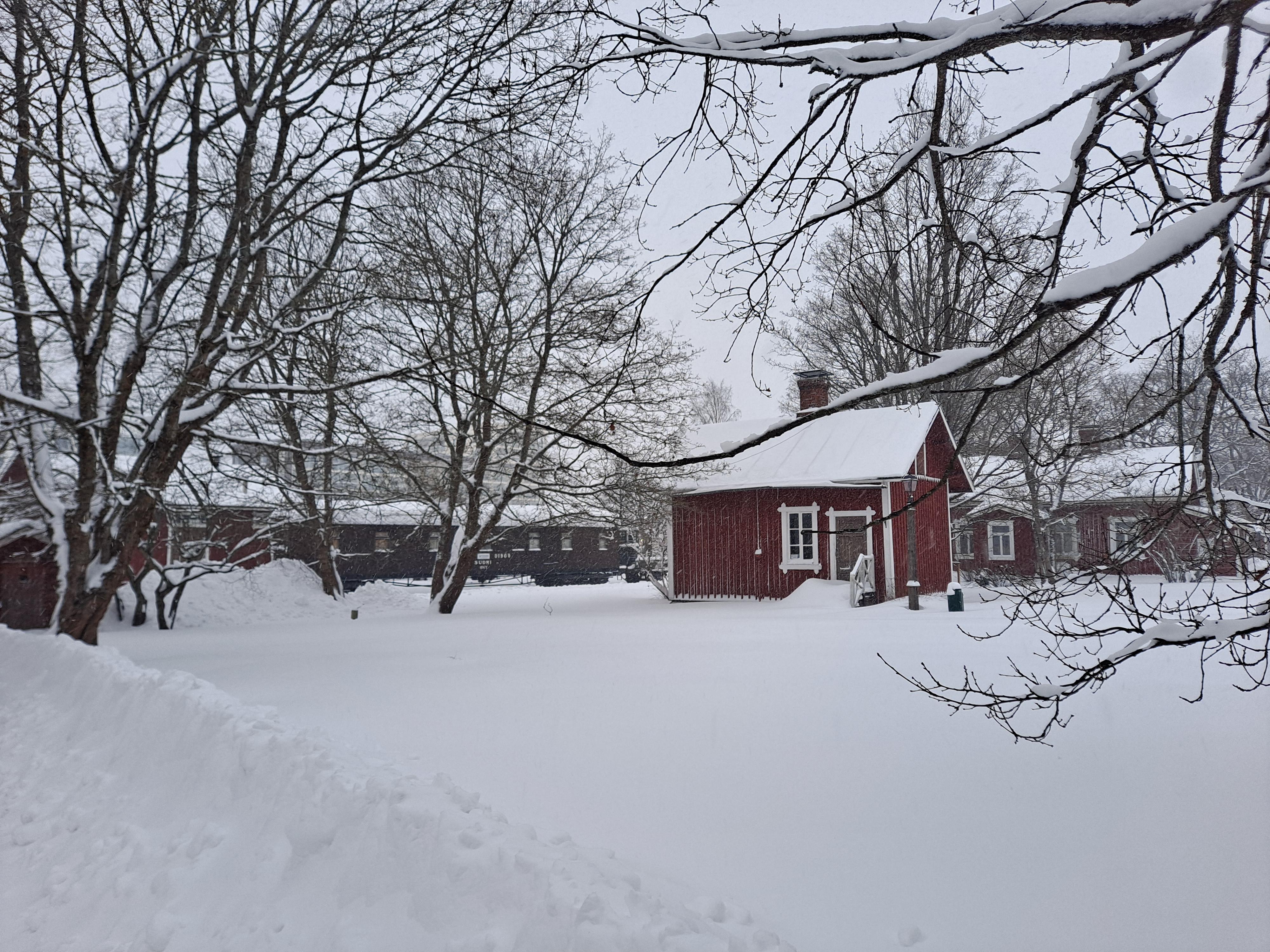 Rautatiemuseon puistossa oleva rautatieläisten pakaritupa ja asuinrakennus keskellä lumista talvimaisemaa.