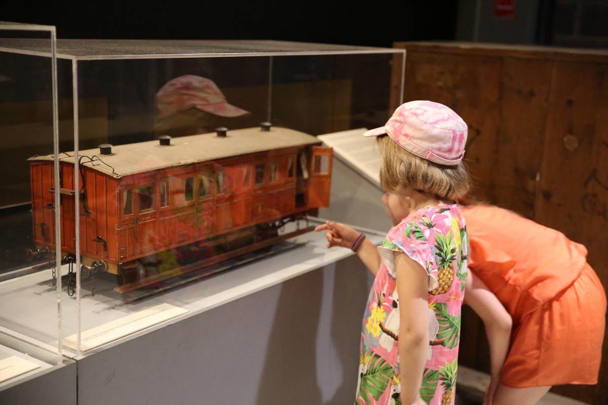 Tytöt katselevat vitriinissä olevaa matkustajavaunun pienoismallia.
