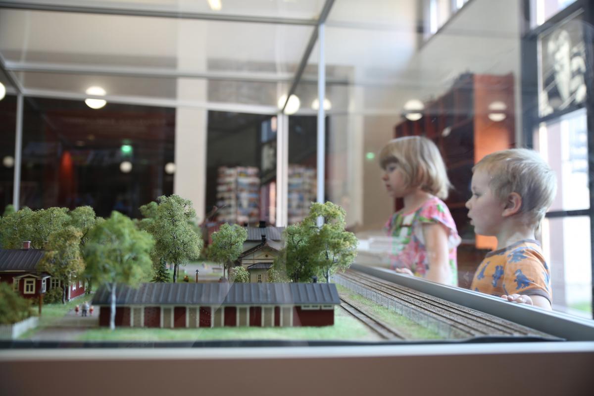Kaksi lasta katselee museon aulassa Rautatiemuseon alueen pienoismallia.