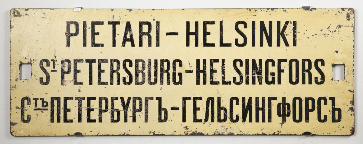 Vaalea määränpääkilpi, jossa lukee Pietari-Helsinki myös ruotsiksi ja venäjäksi.