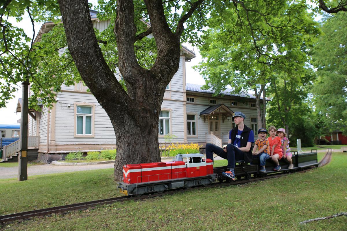 Kolme lasta ja kuljettaja puistojunan kyydissä Rautatiemuseon vehreässä puistossa.