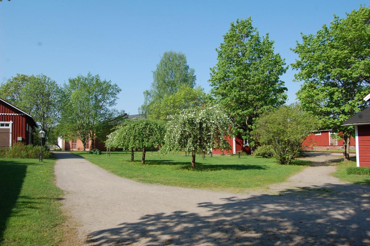 Suomen Rautatiemuseon rautatieläisrakennuksia museon puistossa kevätaikaan.