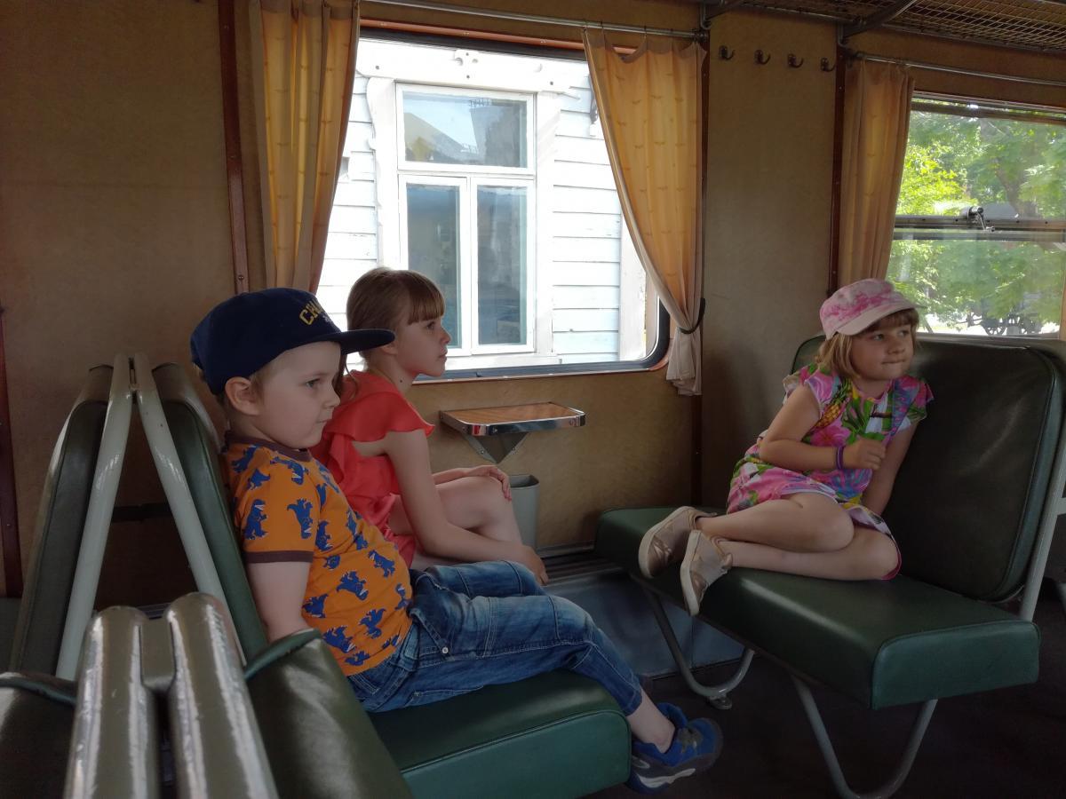 Lapset istumassa Lättähattu-junan penkeillä.